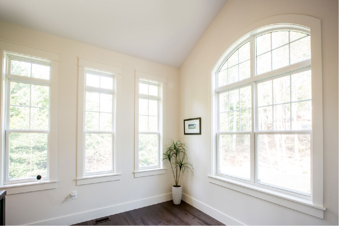 Corner of house with One double arched window and three Single Hung Windows